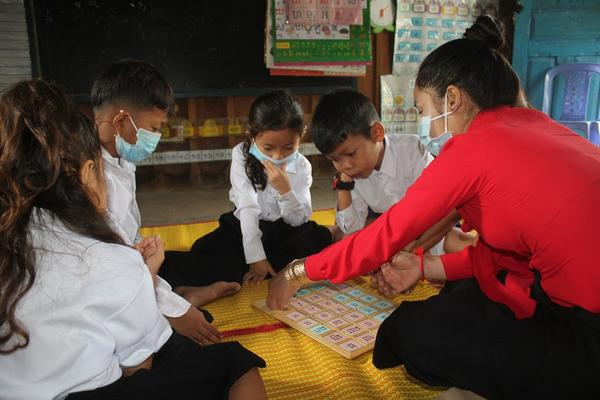 IMG_Teacher guides children to play Khmer consonant puzzle.jpg